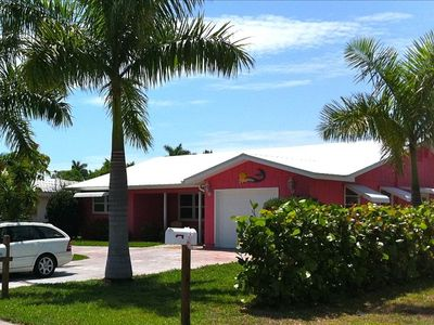 Front of house painted Key West Pink and surrounded with lots of Palm Trees