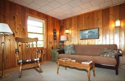 Living room with futon and wood paneled walls.