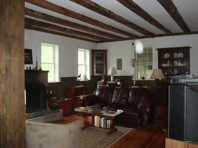 Large Living Room with Wood Fireplace and Hand Hewn Beams