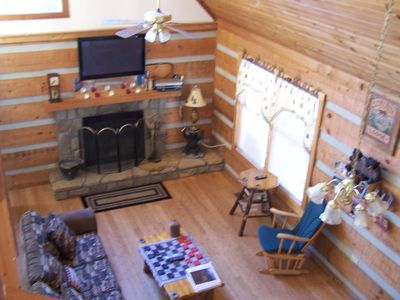 Living room: wood burning fireplace and large flat screen TV; cathedral ceiling