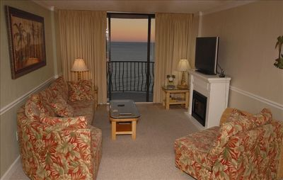 Living area with balcony overlooking the Atlantic. Flat-screen TV and fireplace