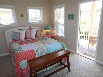 Guest room with queen bed and door to private deck.