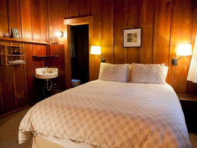 Beautiful shot of queen bedroom shows heart of redwood paneling.