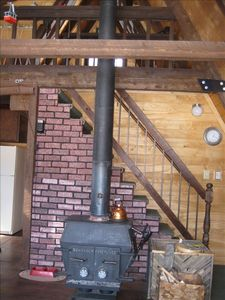 Wood stove in living room, stairs to loft