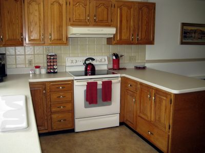 Large kitchen with island, tile backsplash, double porcelain sink.