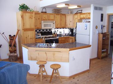 Open kitchen with bar area, separate dining table seats 6