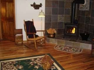 Wood stove surrounded by slate in family room