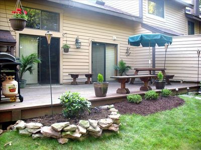 Deck with wood furniture, gas grill, and elegant landscaping.