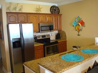 Ocean Reef condo photo - Cheerful kitchen features brand new cabinets and upgraded stainless appliances