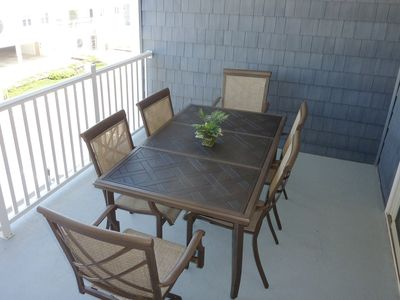 large covered balcony with dining set