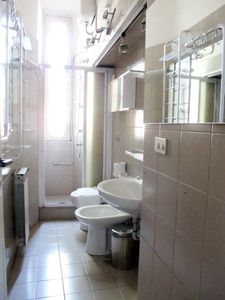 Fully equipped bathroom with shower, toilet, sink and bidet.