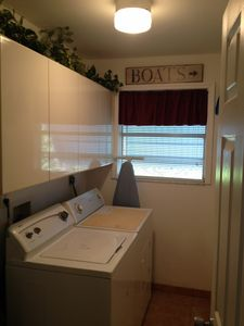 Laundry room has a washer and a dryer. It also has a iron and an iron board.