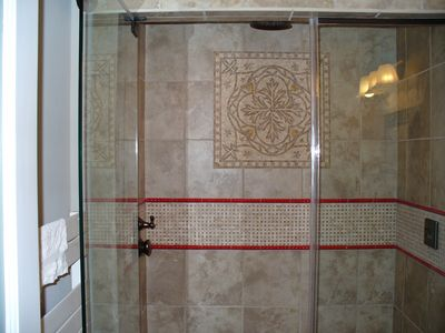 Steam shower, frameless shower door, towel warmer (at left)