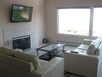 "Living room with leather sofas and 42"" flat panel television"