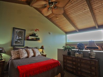 Master bedroom with natural wood vaulted ceilings and tropical fan.