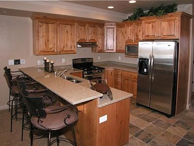 Kitchen with granite counter tops, knotty pine cabinets and stainless appliances