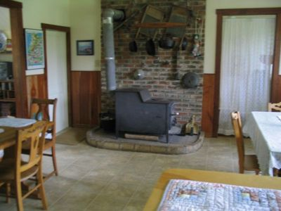 view of the woodstove and dining area in the kitchen