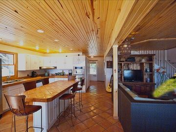 OPEN PLAN KITCHEN/LIVING/DINING ROOM TERROCOTTA TILES - WOOD CEILING