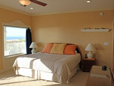 Comfortable kingsize bed with sliding doors out to deck and view of the Beach