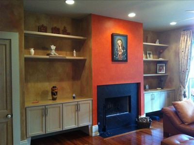 Fireplace in  living room ,original art,pine floors,cedar doors.Opens to patio