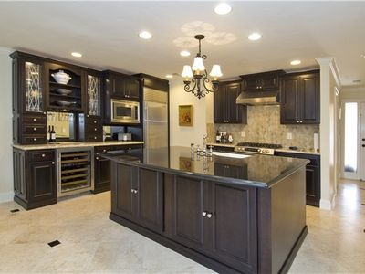 Gourmet kitchen with top of the line appliances, bar area and countertop dining.