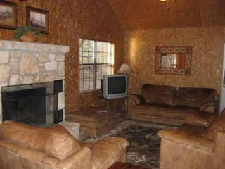 Concan cabin photo - Leather furniture and fireplace
