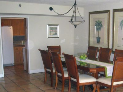 dinning room table and partial view of kitchen side by side freezer fridge