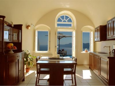 Oia villa rental - Sitting area and kitchen in East Canava. With table and umbrella by the pool