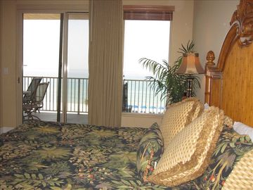 Master bedroom with balcony access and view of the ocean.