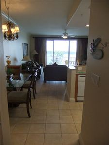 Kitchen, dining and living area as seen from hallway. Balcony overlooks pool.