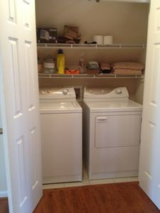 Full sized washer and dryer with laundry supplies provided.
