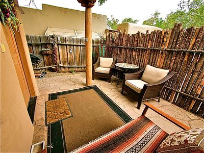 Front entrance outdoor seating, BBQ, large cushioned chairs.