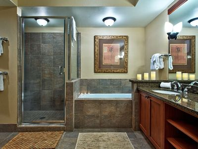 Master bathroom has two sinks, a tub, and a walk-in shower. Hairdryer included.