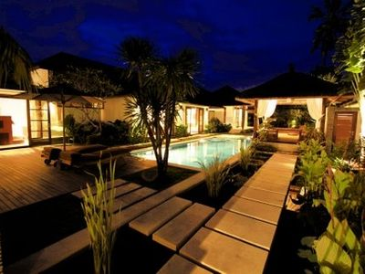 Tropical garden, pond and pool with enchanting night ambiance