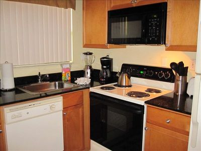 Fully equipped kitchen including dinnerware, appliances,and cookware.
