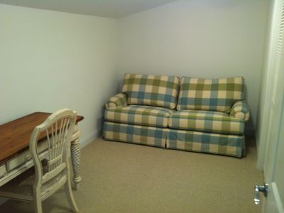 First floor den. The couch has a pull-out bed. There is a closet to the right.