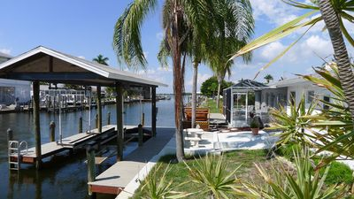 Screened Lanai, Deck w/ Hot Tub, Patio w/ table and 10,000 lb covered Boat Lift.