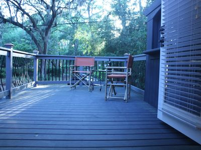 Relax on the upstairs deck under majestic oaks