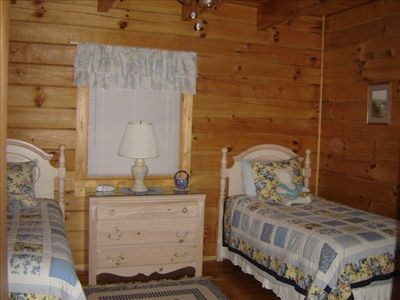 An adorable bedroom with two twin beds a nice size closet & two windows.