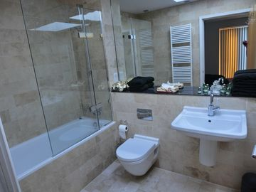 en-suite bathroom with tub with shower