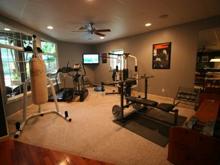 Philadelphia estate photo - Gym with treadmill, elliptical machine, weights, boxing bags & view of tropical