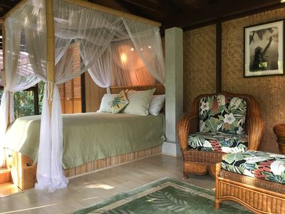 Cottage Interior: Comfy queen bed and rattan lounging chair.