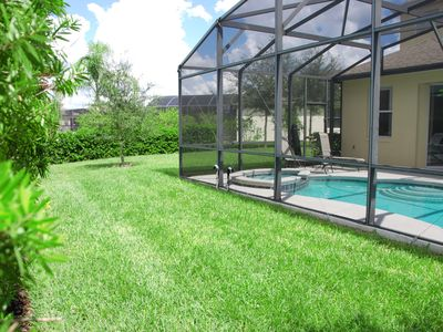 Rear grassed area behind covered pool & spa with insect screening mesh.