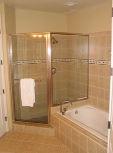 Large master bathroom with his and hers sinks, soaking tub, and walk in closet.