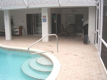 Pool, paver deck/patio area, dining, outdoor gas grill, and fenced yard access.