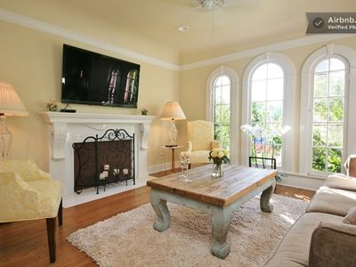 BEAUTIFUL LIVING ROOM WITH TELEVISION, COUCH, COFFEE TABLE, AND CHAIRS