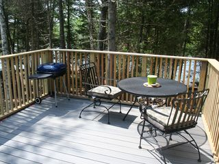 Eastbrook house photo - Deck, charcoal grill, views to lake/woods/fire pit. Table with 4 chairs.