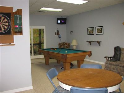 Game room with pool table and dart board.