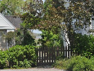 East Quogue house photo - View of gate to vegetable garden, back garden, and bay from gravel driveway.