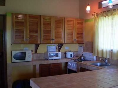 Fully equipped kitchen with breakfast bar, coffee maker, blender and more